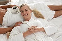 Couple relaxing on hotel bed, woman resting head in man´s lap, man holding coffee, elevated view