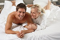 Affectionate couple lying on hotel bed, smiling, front view, portrait