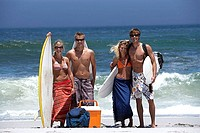 Two young couples standing on beach, carrying surfboards, portrait, sea in background