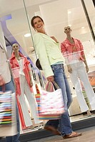 Couple with shopping bags walking past window display in shop, low angle view blurred motion, tilt