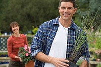 Couple shopping in garden centre, focus on man holding pot plant in foreground, smiling, portrait