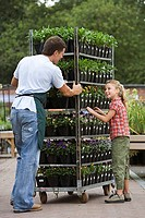 Man working in garden centre, pushing trolley stacked with pot plants, girl 8-10 assisting