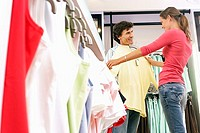 Couple shopping in clothes shop, woman holding yellow top up against boyfriend, smiling, side view