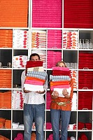 Couple shopping in department store, holding two piles of towels beside shelf, faces obscured