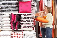 Couple shopping for cushions in department store, side view