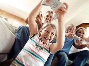 Family sitting on sofa at home, playing with video games console, smiling, low angle view tilt (thumbnail)