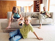 Father reading book on sofa at home, boy 6-8 changing tv channel, girl 6-8 playing video game