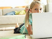 Boy lying on sofa at home, focus on girl 6-8 lying on floor, using laptop, surface level