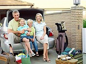 Family sitting on edge of car boot in driveway, luggage on ground, smiling, portrait