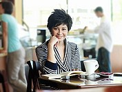Young woman reading book at cafe table, focus on foreground, smiling, portrait (thumbnail)