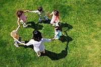 Teacher playing game of ring-a-ring-o´roses with children 3-5 on grass, overhead view