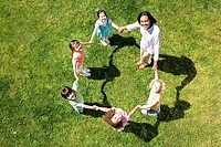 Teacher playing game of ring-a-ring-o'roses with children 3-5 on grass, portrait, overhead view