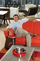Man with shopping bags sitting on new red sofa in furniture store, smiling, portrait