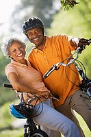 Active senior couple standing with bicycles in park, smiling, portrait tilt
