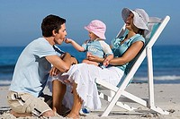 Family relaxing on beach, girl 2-3 sitting in mother's lap, feeding father, laughing, side view