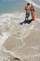 Two generation family standing in surf at beach, mother carrying daughter 2-3, elevated view