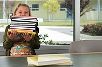 Girl 9-11 carrying stack of books in classroom, face obscured, front view, portrait