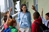 Female teacher talking to class outside school, children 9-12 with hands raised