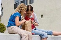 Two girls 9-11 sitting on wall outside school, looking inside paper bag