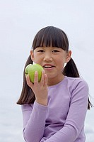 Girl 9-11 eating green apple, smiling, front view, close-up, portrait