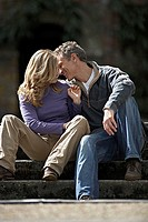 Affectionate couple sitting on steps, man whispering in woman´s ear, smiling