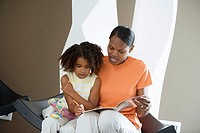 Mother and daughter 5-7 sitting at home, girl colouring picture in book with felt tip pen