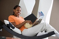 Woman relaxing in curved chair at home, reading magazine, feet up, smiling, side view, portrait tilt