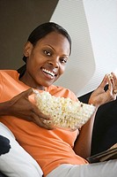 Woman relaxing at home, eating popcorn, smiling, side view, close-up, portrait tilt