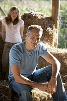 Couple in barn, focus on man sitting on bale of hay in foreground, smiling, portrait