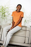 Woman wearing orange t-shirt and white trousers, sitting on edge of sofa at home, smiling, portrait tilt