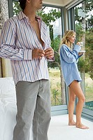 Couple relaxing in bedroom, woman in man's shirt drinking cup of tea, man getting dressed