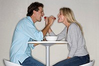 Couple sitting at table in kitchen, feeding each other strawberries, face to face, smiling, profile