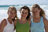 Three teenage girls 13-15 standing on beach, smiling, front view, portrait
