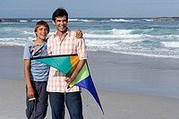 Father and son 13-15 standing on beach with kite, smiling, front view, portrait