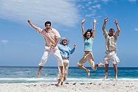 Two couples jumping on beach, smiling, front view, portrait, sea in background