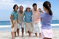 Multi-generational family standing on beach, girl 6-8 filming with camcorder, smiling