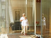 Senior couple standing on patio beside sliding doors, smiling, portrait
