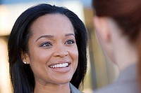 Businesswoman talking to colleague, smiling, close-up differential focus