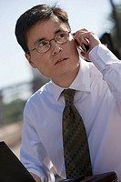 Businessman in spectacles using laptop and mobile phone, outdoors, side view tilt