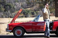 Man standing at roadside beside red convertible car with engine trouble, using mobile phone