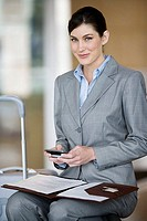 Businesswoman with folder in lap, holding mobile phone, smiling, portrait