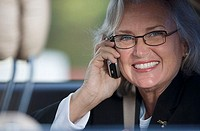 Senior businesswoman in spectacles using mobile phone, smiling, close-up, portrait