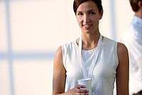 Woman in white sleeveless top holding disposable cup, smiling, front view, portrait