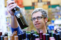 Man shopping for wine in supermarket, choosing bottle from shelf, smiling
