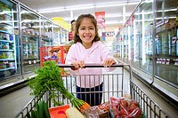 Girl 4-6 shopping in supermarket, pushing trolley in aisle, smiling, front view, portrait