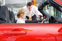 Woman sitting in red convertible car in showroom, salesman assisting, side view, focus on foreground