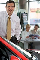 Couple looking at brochure in car showroom, focus on salesman in foreground, smiling, portrait