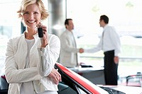 Salesman shaking hands with customer in car showroom, focus on woman with key, smiling, portrait
