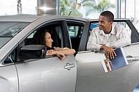 Couple looking at new silver saloon in car showroom, man holding brochure, woman in driver's seat