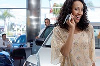 Salesman and customer in car showroom, focus on woman holding key beside new car, smiling, portrait